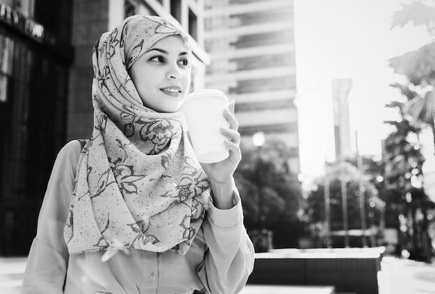 Islamische frau, die kaffee in der stadt trinkt