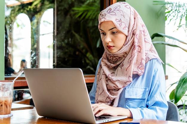 Islamische frau, die laptop sitzt und verwendet