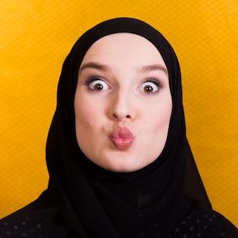 Islamische frau, die lustiges gesicht gegen gelbe oberfläche bildet