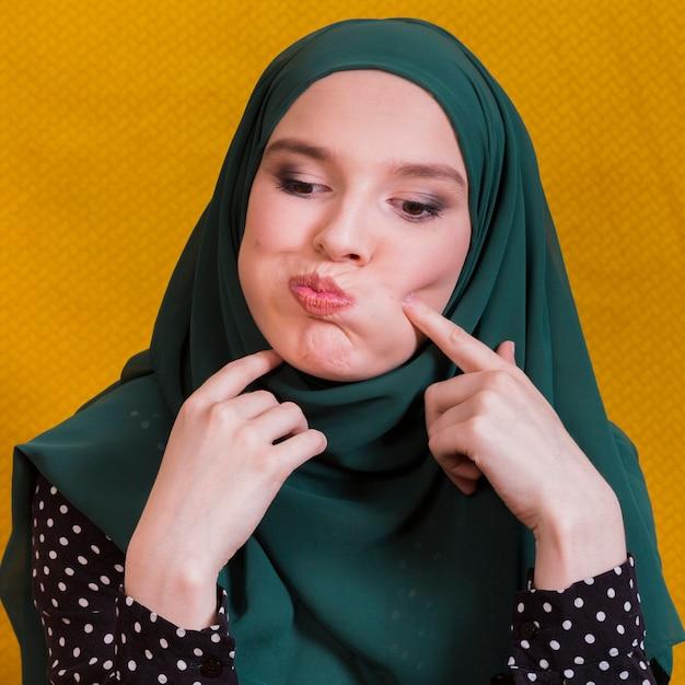 Islamische frau, die lustiges gesicht gegen gelben hintergrund bildet