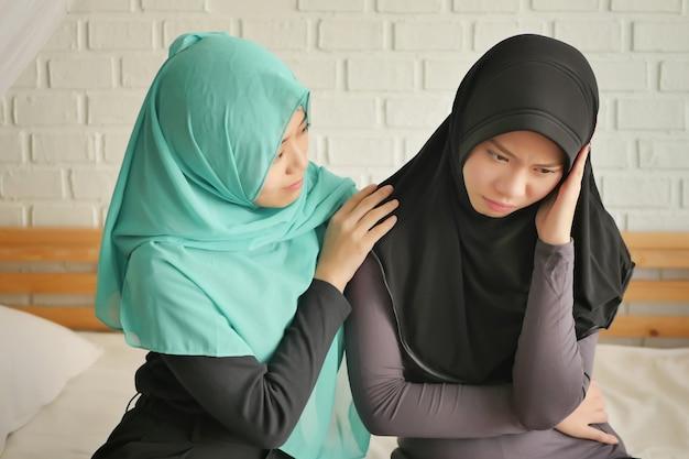 Islamische frau, die sich um ihren kranken freund oder familienangehörigen kümmert; kranke kopfschmerzen islam muslimische frau, die von ihrer besten freundin betreut wird; kranke frau mit schmerzen mit vertrauenswürdigem freundkonzept