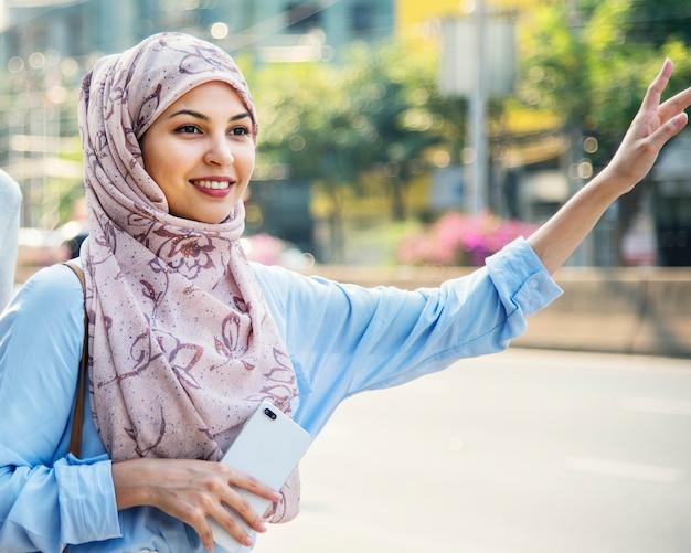 Islamische frau, die taxi in der stadt nennt