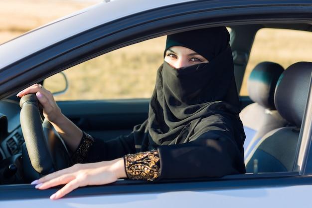 Islamische frau in nationaltracht beim autofahren