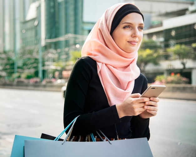 Islamische frau mit einkaufstüten und handy halten