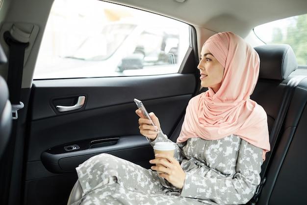 Islamische frau mit gerät im taxi