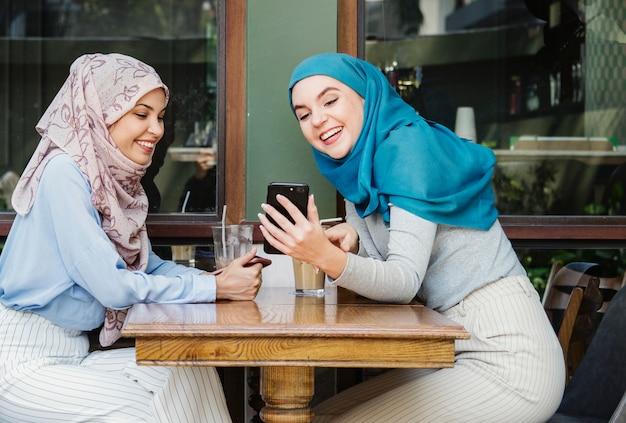 Islamische freunde, die am intelligenten telefon sprechen und schauen