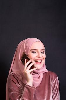 Islamische lachende frau des zaubers bei der unterhaltung auf mobiltelefon vor schwarzem hintergrund