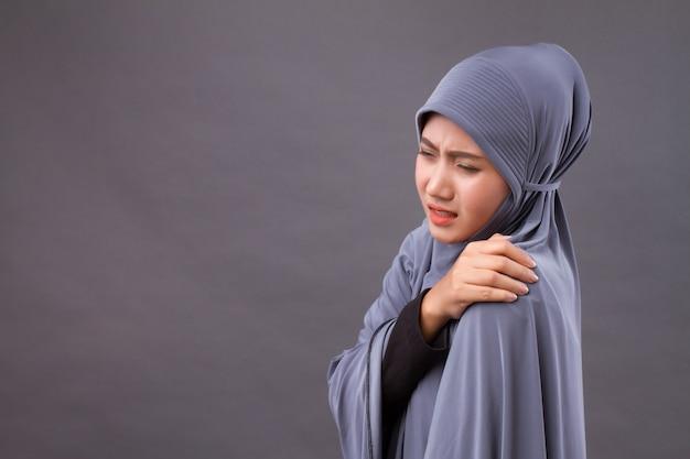 Islamische muslimische frau mit schulter- oder nackenschmerzen, steifheit, verletzung