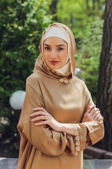Islamische schöne frau in einem muslimischen kleid, das auf einem sommerparkstraßenhintergrundwald-herbstbäumen steht