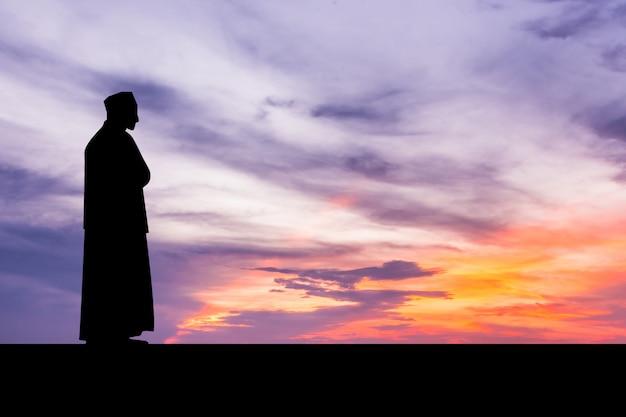 Islamischer mann, der moslemisches gebet in der dämmerungszeit betet