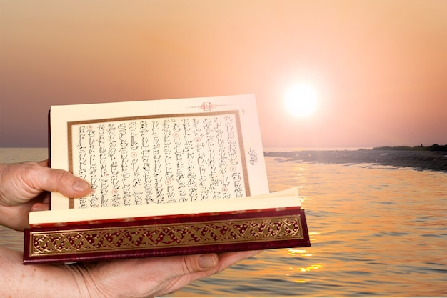 Islamisches buch koran in den händen auf hintergrund
