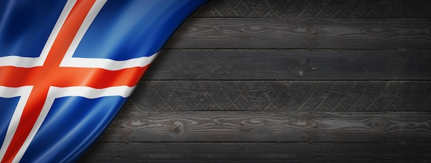 Island-flagge auf schwarzer holzwand. horizontales panorama-banner.