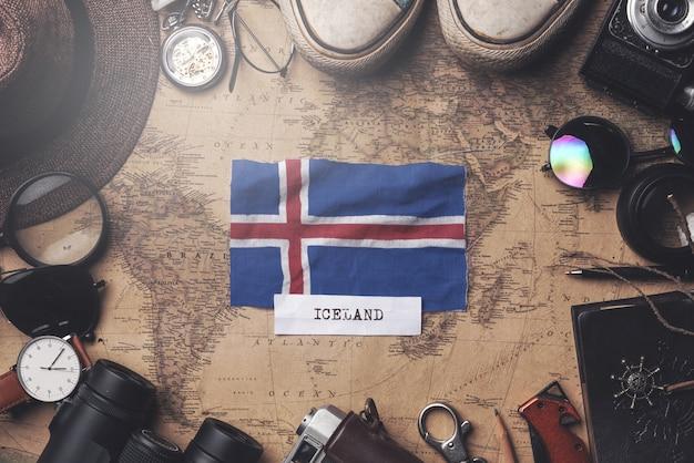 Island-flagge zwischen dem zubehör des reisenden auf alter weinlese-karte. obenliegender schuss