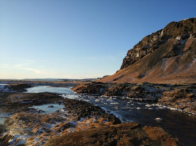 Islands atemberaubende berglandschaft im winter, ein fluss mit wasserfall. naturfarben.