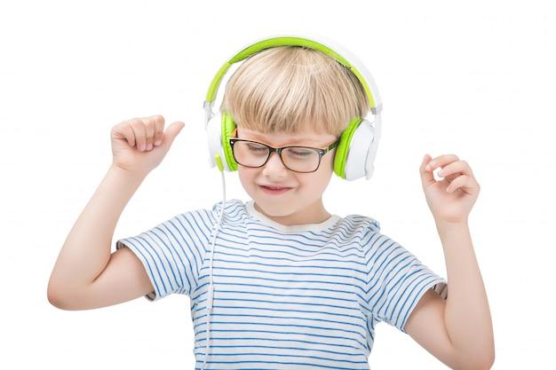 Isoliert auf weißem niedlichem kind, das die musik auf kopfhörern hört. junge auf weißem hintergrund mit kopfhörern.