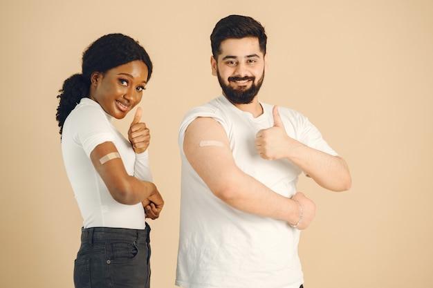 Isoliert, beige hintergrund. afrikanische frau und mann, die sich daumen zeigen. impfung gegen covid.