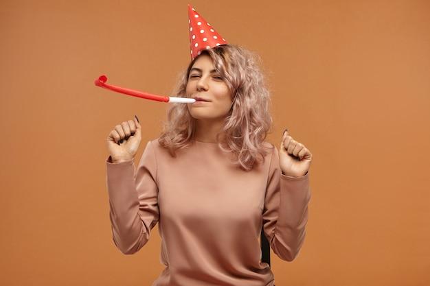 Isoliert von attraktiver fröhlicher glücklicher junger frau, die stilvolles oberteil und rote kegelkappe trägt, die pfeife blasen und tanzen, überglücklichen gesichtsausdruck haben, ihren geburtstag feiern