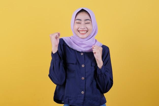 Isoliert von schönen frauen, die erfolg haben, indem sie hijabs tragen, geballte fäuste heben, den sieg feiern und auf dem gelben hintergrund sehr glücklich und glücklich sind