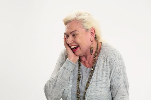 Isolierte ältere dame lachen. fröhliche frau, die ihr gesicht berührt. großartiger sinn für humor.
