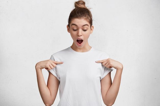 Isolierte aufnahme der attraktiven frau mit erstauntem blick, hält den mund weit offen, zeigt auf leeres t-shirt an, posiert vor weißem studiohintergrund, drückt überraschung aus. menschen, kleidung, werbung