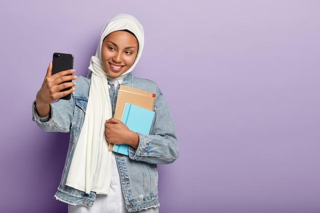 Isolierte aufnahme der entzückten frau trägt traditionellen hijab