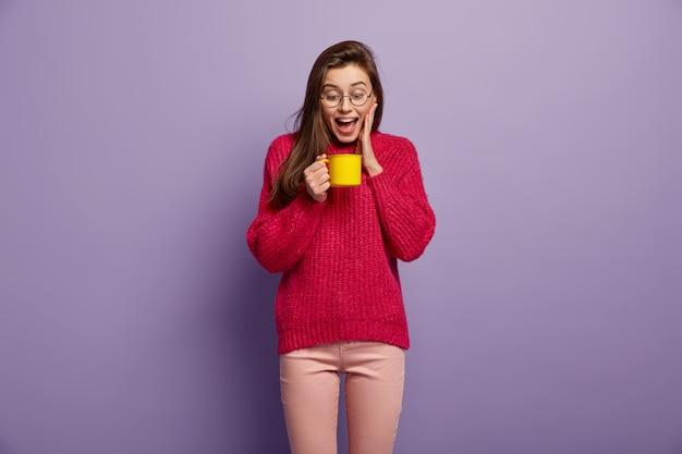 Isolierte aufnahme der glücklichen überglücklichen frau schaut auf tasse des heißen aromatischen getränks, hält gelben becher, trägt brille, roten pullover, steht gegen lila wand. freudige frau hat kaffeepause. trinkkonzept