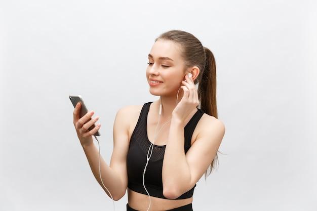 Isolierte aufnahme der jungen sportlerin hat einen gesunden athletischen körper, hört musik mit kopfhörern, hält smartphone.