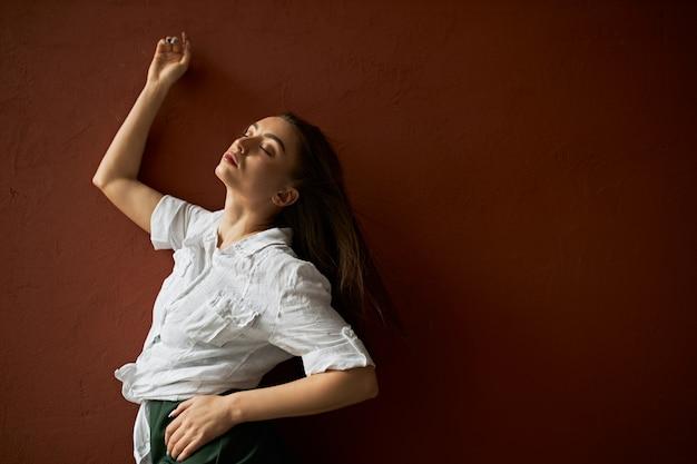 Isolierte aufnahme der sinnlichen attraktiven frau mit losen langen braunen haaren, die augen im genuss schließen, sich zurücklehnen auf leere kopierraum-studiowand, erfreuten blick, erhöhen auf hand, tragen des weißen hemdes