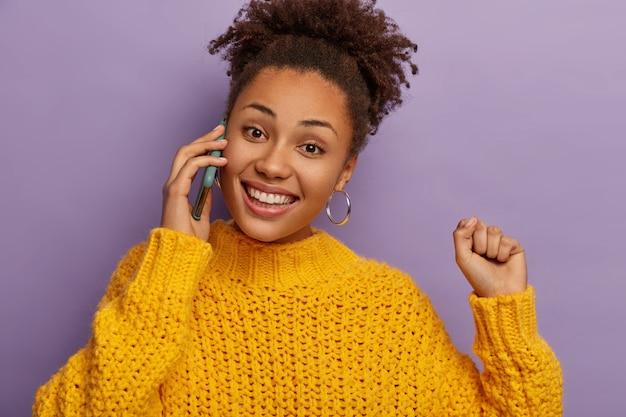 Isolierte aufnahme des glücklichen freudigen weiblichen teenagers genießt unterhaltung, telefone über mobiltelefon, lächelt breit, hebt den arm, gekleidet in winterkleidung
