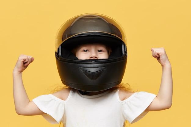 Isolierte aufnahme des rennfahrers des kleinen mädchens, das gegen gelbe wand posiert, die schwarzen sicherheitsmotorradhelm trägt, der ihre bizepsmuskeln demonstriert. menschen, extremsport und adrenalin-konzept