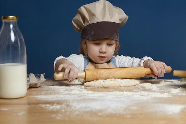 Isolierte aufnahme des schönen kleinen mädchens des europäischen aussehens, das nudelholz hält, während kekse oder anderes gebäck an kulinarischer werkstatt machen