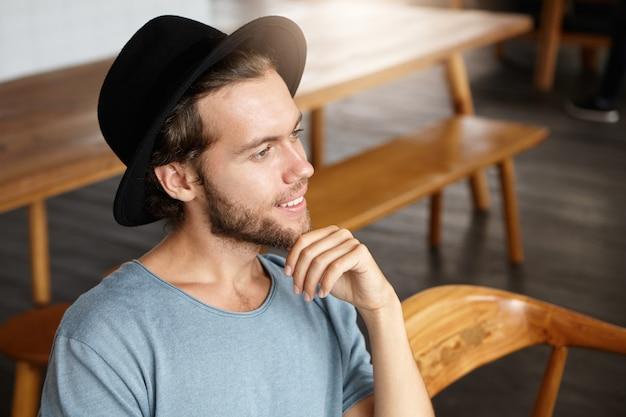 Isolierte aufnahme des stilvollen jungen hipsters in der trendigen kopfbedeckung, die sein kinn berührt und in der bar oder im restaurant sitzt