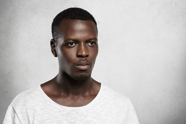 Isolierte aufnahme des stilvollen modischen afrikanischen modells gekleidet im weißen t-shirt mit ernstem ausdruck.