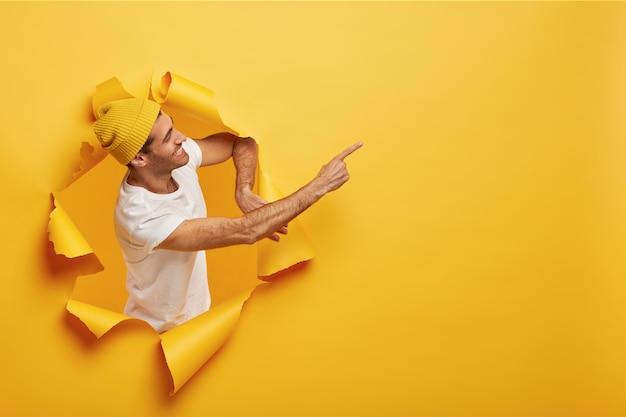 Isolierte aufnahme des zufriedenen männlichen modells steht seitlich im papierloch, gekleidet in gelbe kopfbedeckung