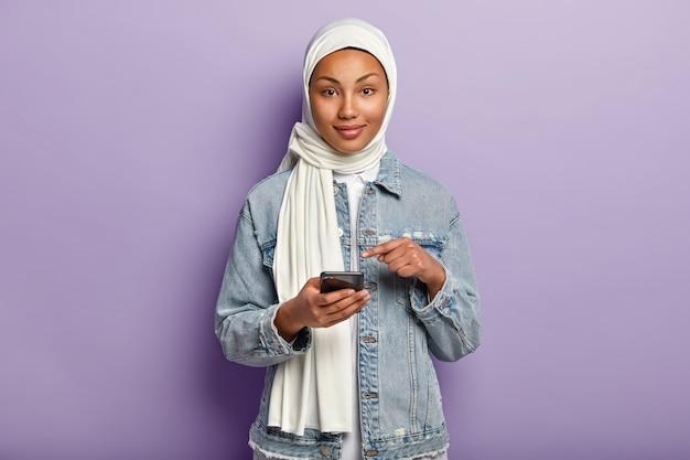 Isolierte aufnahme einer erfreuten jungen frau gemischter rasse mit dunkler haut, folgt muslimischer religion, zeigt auf handy-bildschirm, bittet, internetnachrichten auf der website zu lesen, isoliert über lila wand.