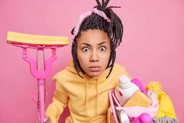 Isolierte aufnahme einer fassungslosen afro-amerikanerin posiert mit reinigungsset starrt an