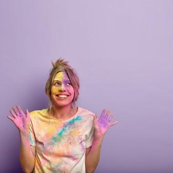 Isolierte aufnahme einer fröhlichen verträumten jungen frau, die nach oben gerichtet ist, beide hände hebt und farbige handflächen zeigt, positiv lächelt, das holi festival of colours feiert, oben freien platz für ihre informationen