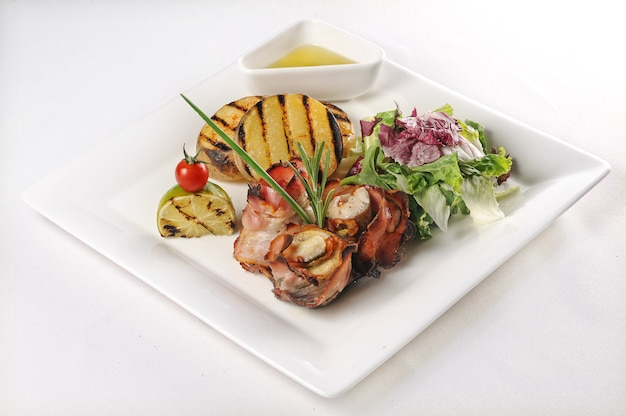 Isolierte aufnahme einer platte mit schweinefleisch mit tomaten und salat