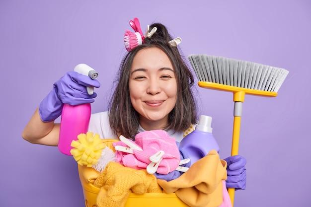 Isolierte aufnahme einer positiven brünetten asiatischen hausfrau hält reinigungsmittel für die reinigung hält besenposen in der nähe des wäschekorbs führt die desinfektion des hauses einzeln über violettem hintergrund durch. fröhliche haushälterin