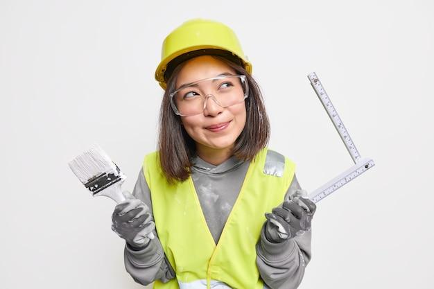 Isolierte aufnahme einer verträumten jungen asiatischen baumeisterin denkt über die gestaltung des hauses nach, hält malpinsel und maßband isoliert auf weiß