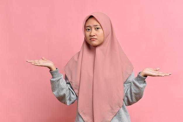 Isolierte aufnahme einer verwirrten schönen muslimischen frau mit hijab, breitet die hände seitwärts aus, grinst das gesicht, fühlt zweifel, während sie die wahl trifft, einzeln auf rosafarbenem hintergrund