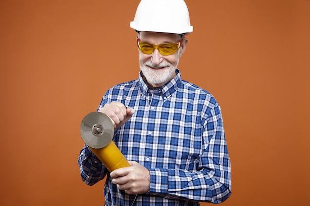 Isolierte aufnahme eines lächelnden unrasierten gealterten kaukasischen handwerkers oder monteurs, der schutzhelm und brille unter verwendung des winkelschleifers zum schneiden und schleifen trägt. schwerarbeits-, bau- und metallkonzept