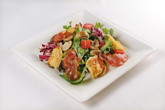 Isolierte aufnahme eines tellers mit salat mit huhn und speck - perfekt für einen lebensmittelblog oder eine menüverwendung