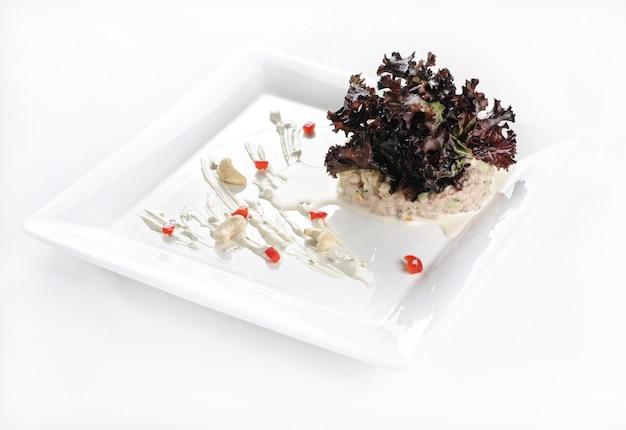 Isolierte aufnahme eines weißen tellers mit einem köstlichen salat - perfekt für einen lebensmittelblog oder eine menüverwendung