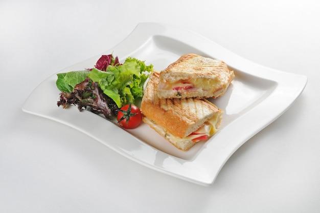 Isolierte aufnahme eines weißen tellers mit einem zweiteiligen sandwich - perfekt für einen food-blog oder eine menüverwendung