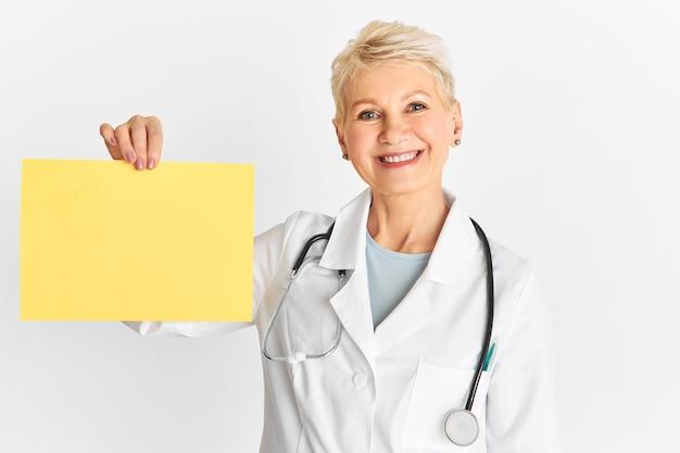 Isolierte aufnahme von gut aussehenden optimistischen älteren ärztin mit blonden elfenhaaren und fröhlichem selbstbewusstem lächeln, das leeres gelbes banner mit kopienraum hält