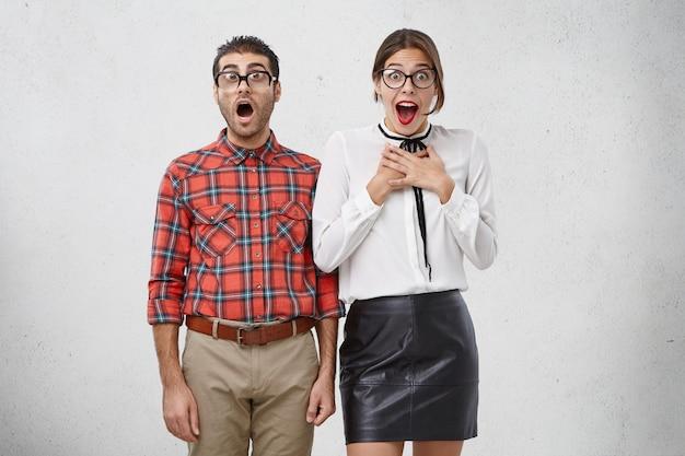 Isolierte aufnahme von ungeschickten jungen weiblichen und männlichen wins mit aufgeregtem oder überraschtem ausdruck