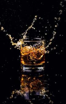Isolierte aufnahme von whisky mit spritzer auf schwarzem hintergrund
