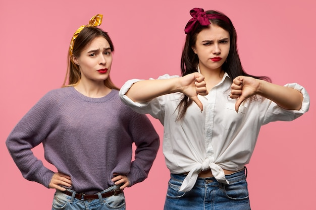 Isolierte aufnahme von zwei attraktiven jungen frauen, die missbilligung, abneigung ausdrücken, von schlechter qualität enttäuscht sind, daumen nach unten zeigen, missfallenes aussehen haben.