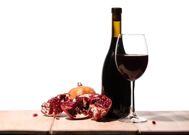 Isolierte burgunderrote rotweinflasche, weinglas und saftiger granatapfel